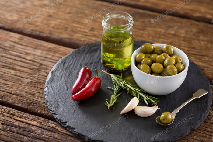 Green olives, fresh herbs with olive oil and red chilies on table