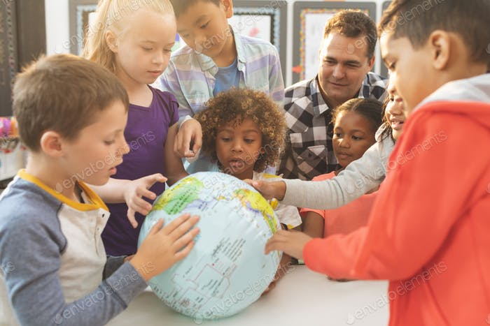 Schullehrer diskutiert über der Erde Globus im Klassenzimmer in der Schule