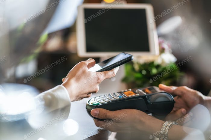 Closeup Asian customer man hand paying money via contactless channel by mobile banking