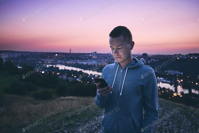 Man using phone at sunrise