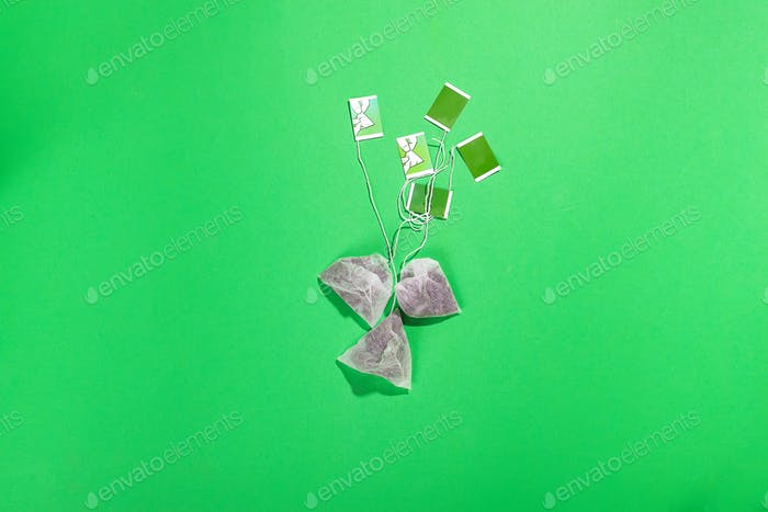 Teabags with green label Isolated on green background, flat lay with copy space
