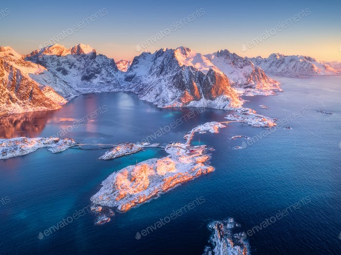 Beautiful landscape with blue sea, snowy mountains at sunrise