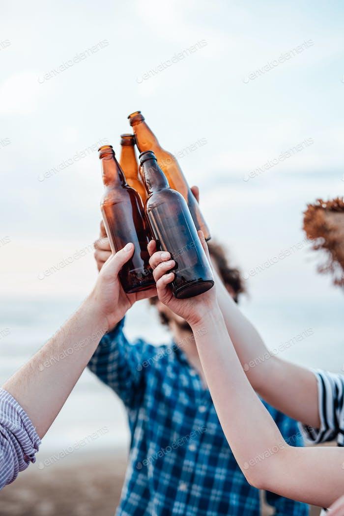 Best friends raise brown beer bottles