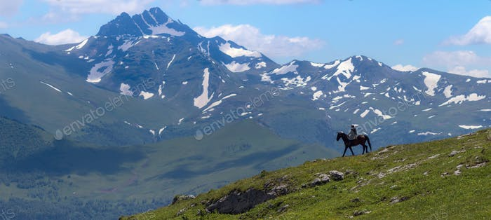 Mountain landscape and shepherd on horse. In the background - mount Magisho. Caucasus mountains.