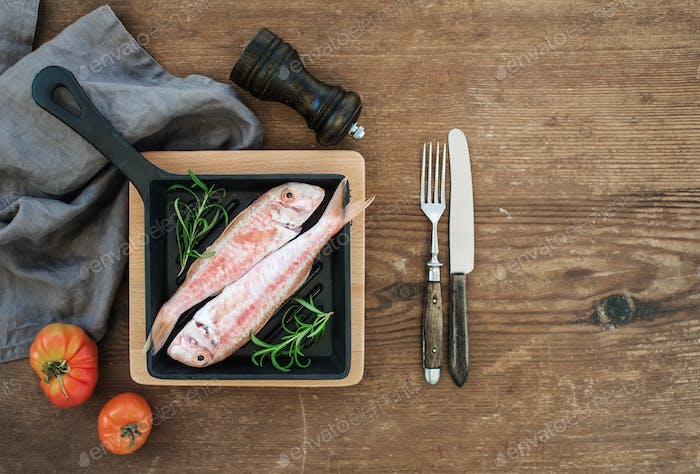 Raw uncooked Red Mullet fish in a cooking pan with rosemary