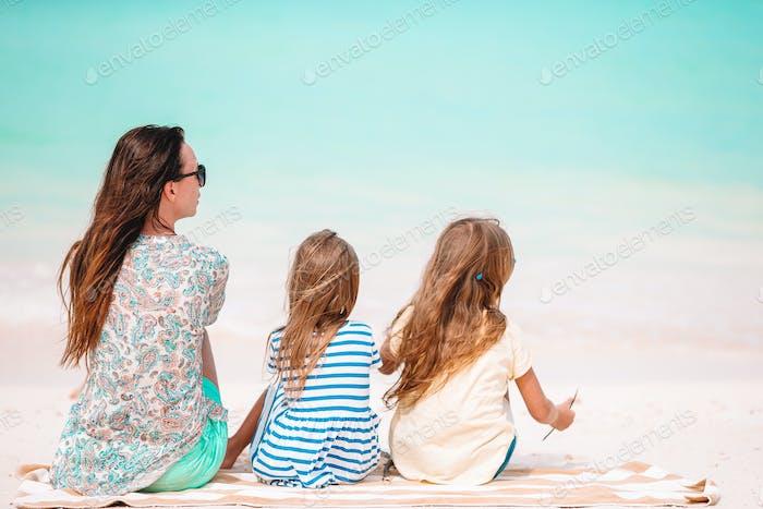 Adorable kleine Mädchen und junge Mutter auf tropischen weißen Strand