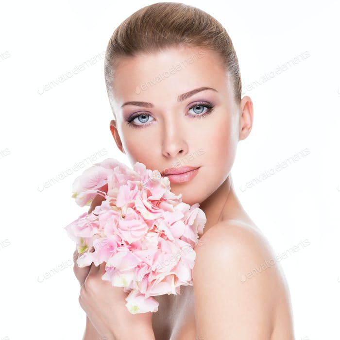 Portrait of young beautiful woman with flowers at face