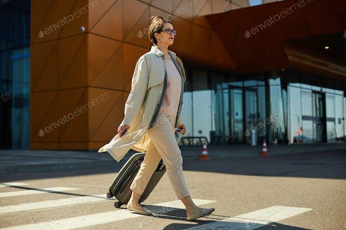 Selbstbewusste Frau mit Gepäck Überquerung Straße