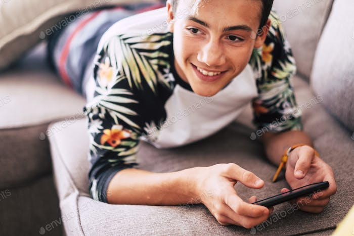 teenager watching videos or playing games in a smart phone in winter lying on a sofa