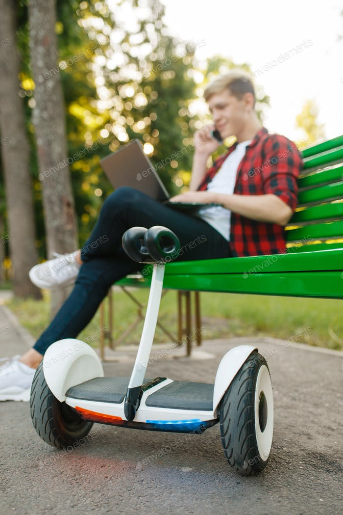 Man with gyroboard sitting on the bench in park