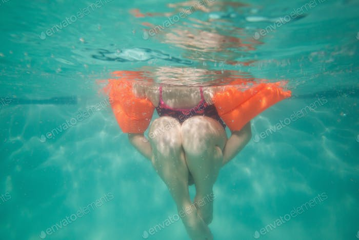 Cute kid posing underwater in pool at the leisure center