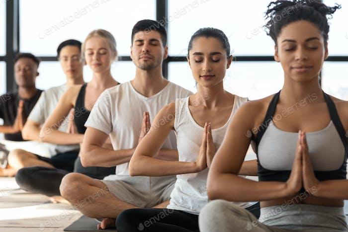 Geist Harmonie. Gruppe von jungen sportlichen Yoga-Liebhabern, die gemeinsam im Studio meditieren
