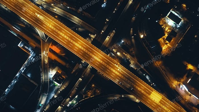 Top down of traffic road lit by lanterns at night illuminate aerial view. Metropolis cityscape