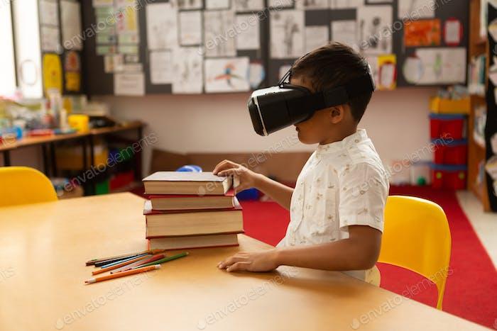 Seitenansicht von Mixed-Race-Schuljungen mit Virtual Reality Headset am Schreibtisch in einem Klassenzimmer