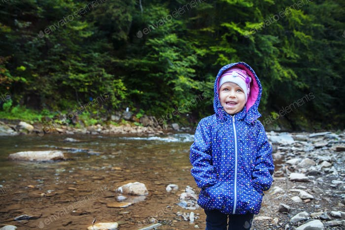 baby standing beside the river laughs. The concept of travel and childhood.