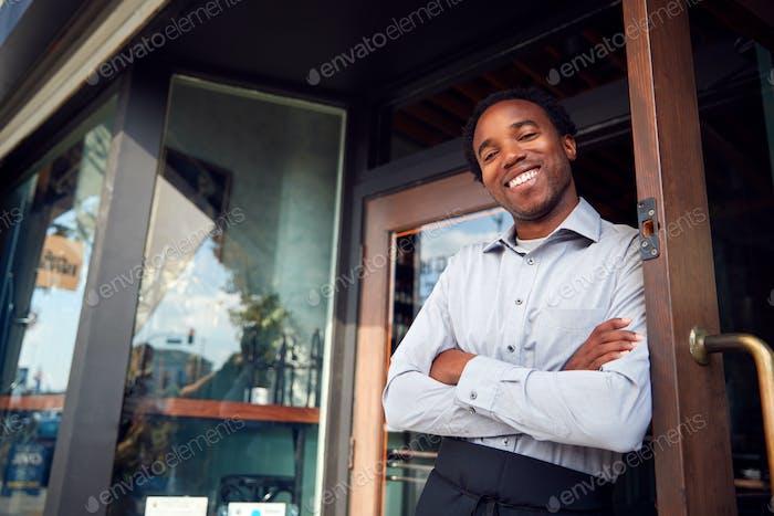 Portrait Of Male Owner Of Start Up Coffee Shop Or Restaurant Standing In Doorway