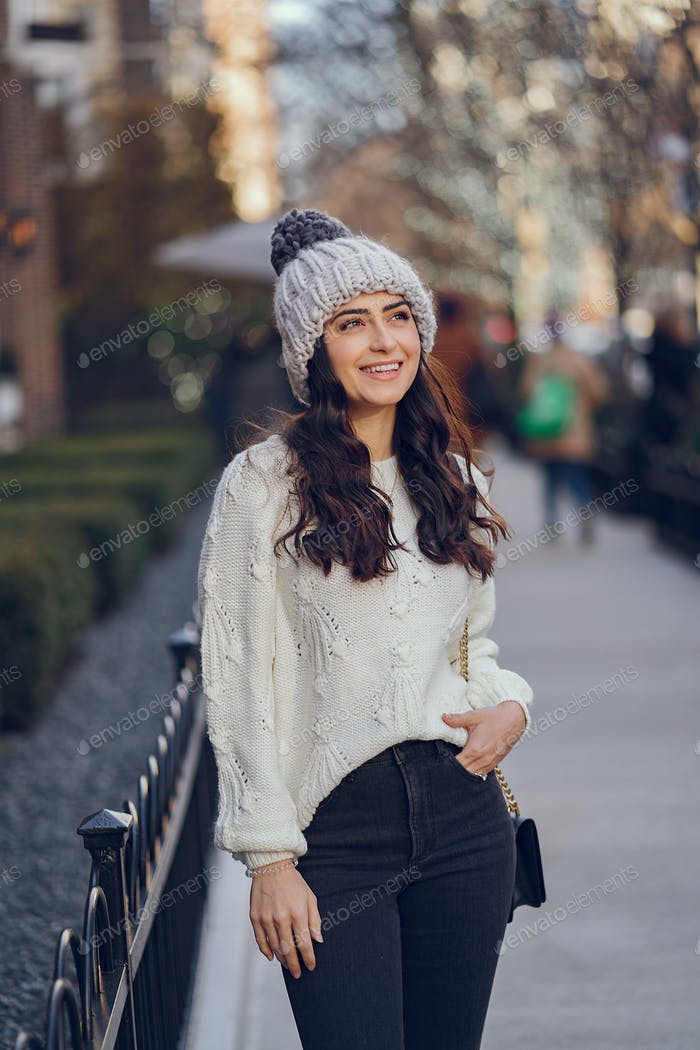 Cute brunette in a white sweater in a city