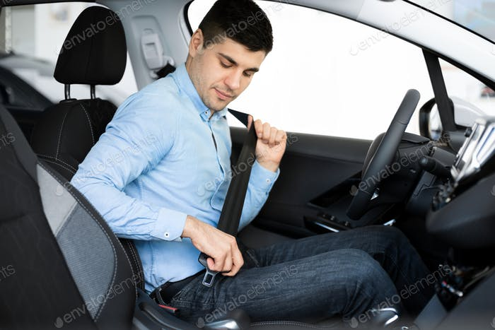 Guy Putting On Seat Belt Sitting In Car