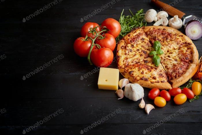 Köstliche italienische Pizza serviert auf schwarzem Holztisch