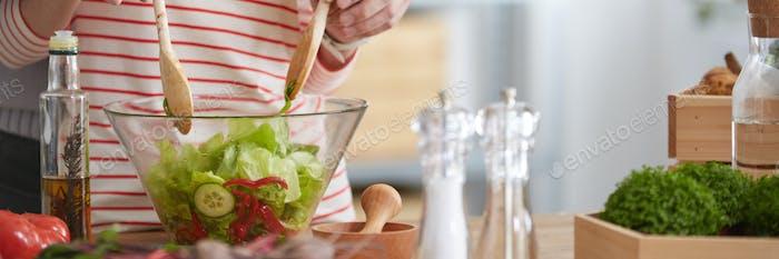 Cook mixing a salad