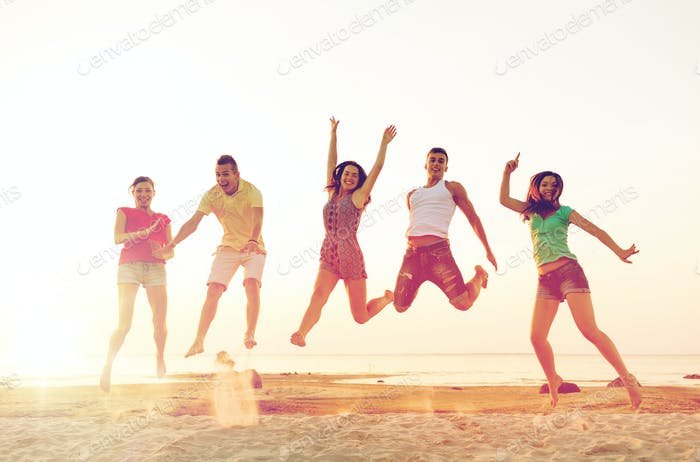 lächelnde Freunde tanzen und springen am Strand