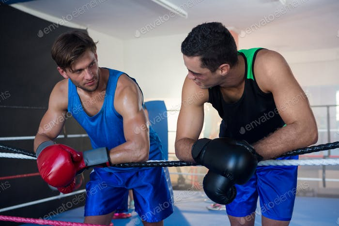 Young male boxers leaning on rope