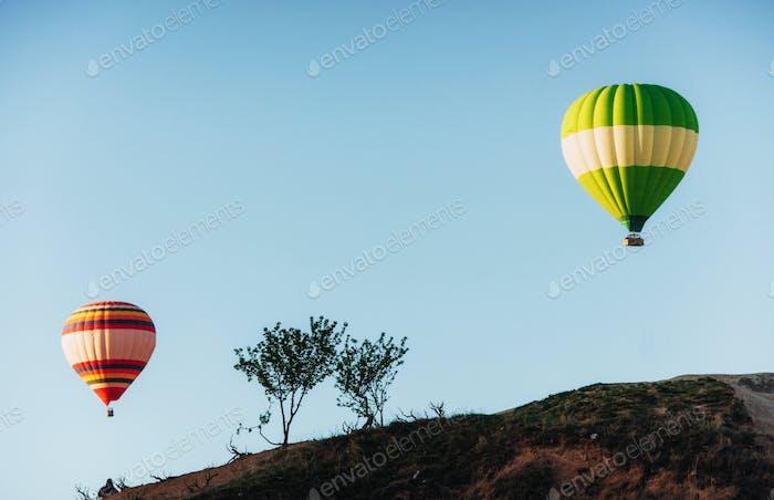 Hot air balloon flying over rock landscape at Cappadocia Turkey. Valley, ravine, hills
