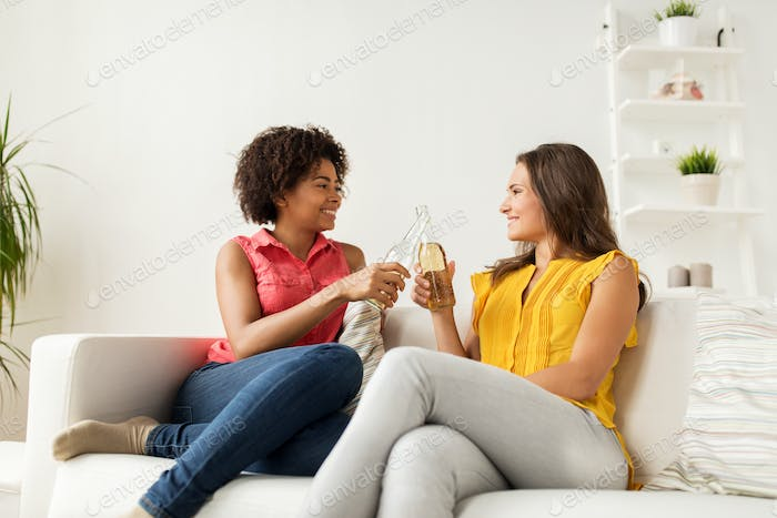 happy women clinking bottles of beer at home