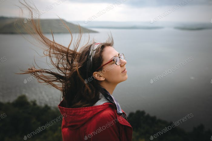 Young carefree woman in glasses relaxing on cliff