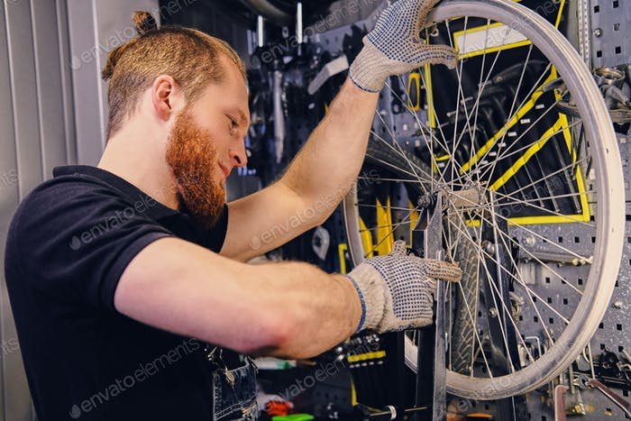 Mechanic removing bicycle rear cassette in a workshop.