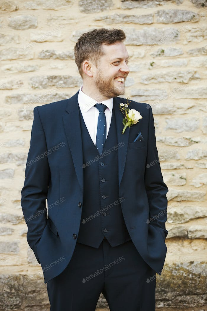 A man in a suit with a buttonhole with his hands in his pockets, smiling.