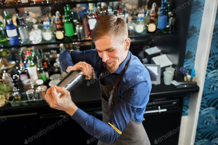 happy barman with shaker preparing cocktail at bar