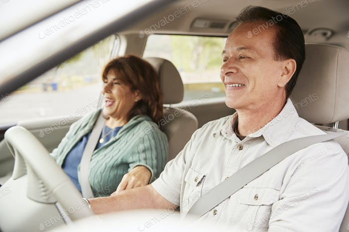 Senior mixed race couple sit smiling in car