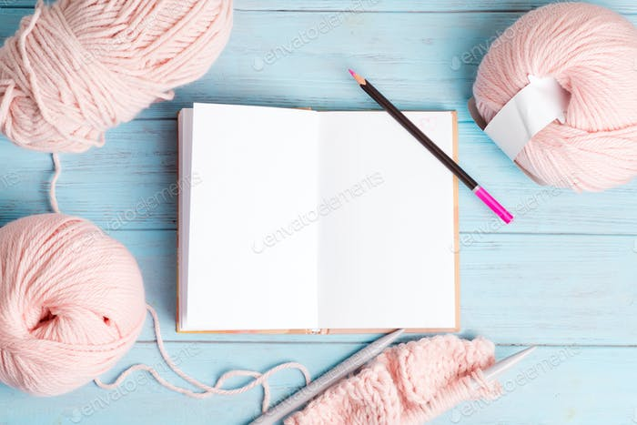 Top view of winding wools and blank notebook for notes and knitting pattern on a light blue wooden