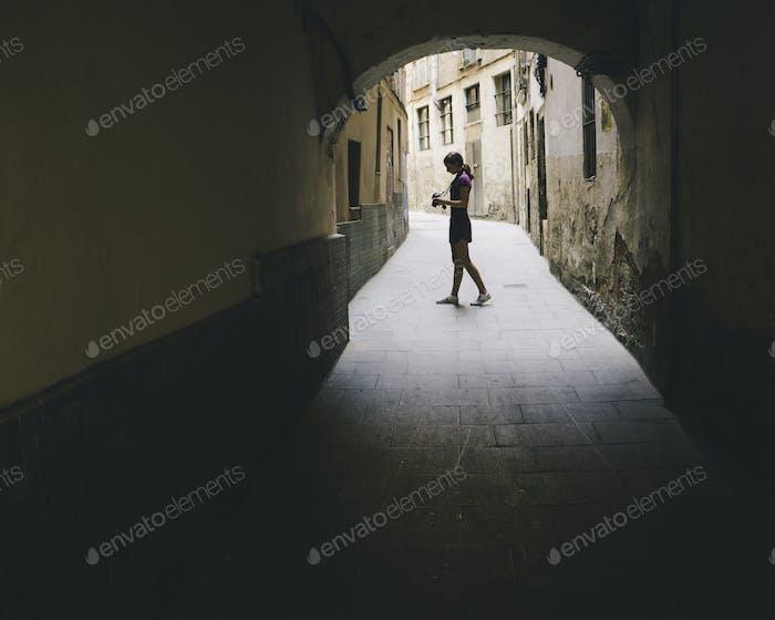 Teenage girl composing photo with digital camera, Gothic Quarter, Barcelona, Spain.