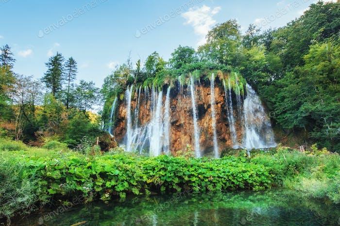Waterfalls in national park falling into turquoise lake. Plitvice, Croatia