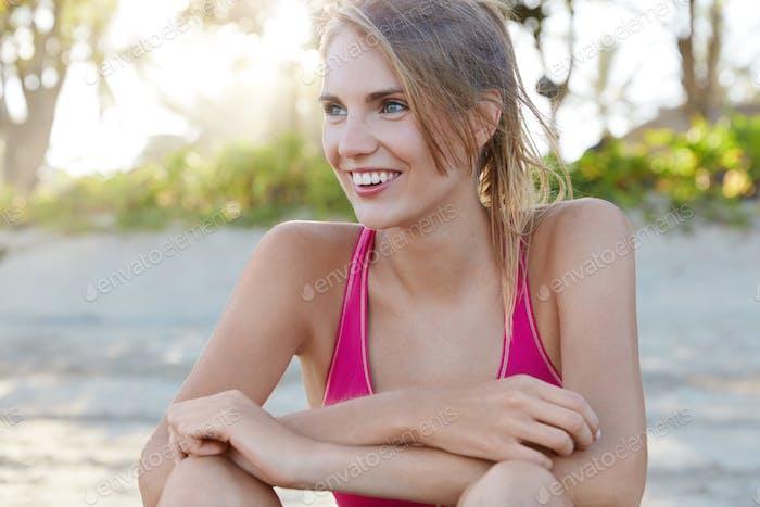 Sportlerin ist mit Outdoor-Aktivitäten bei sonnigem Sommerwetter zufrieden, Müdigkeit aber froh