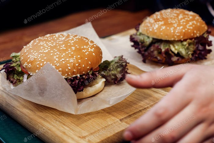 Вкусный бургер. сервировка чизбургер или гамбургер с салатом на деревянном столе