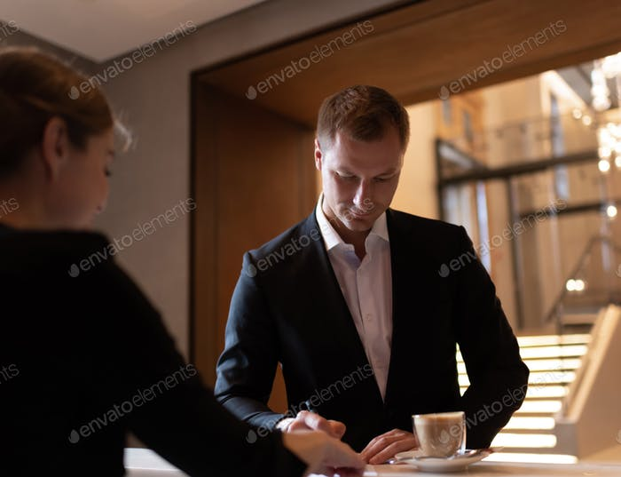 Businessman signing receipt for checkout from hotel