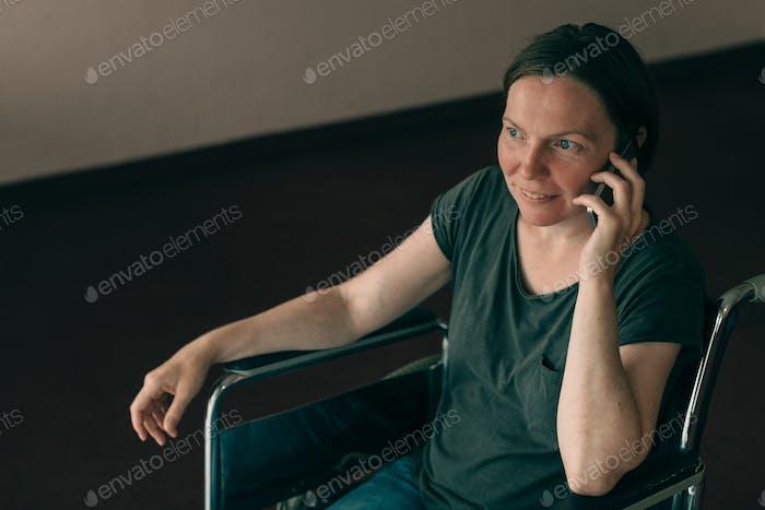 Hoffnungsvolle weibliche Person mit Behinderung im Gespräch auf dem Handy