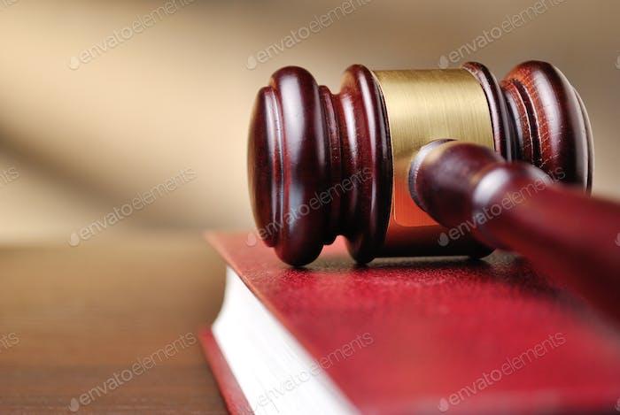 Los jueces de madera martillan en un libro de leyes