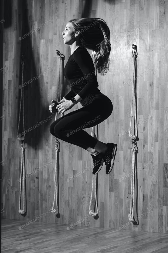 Black and white photo of a slender girl dressed in a black sportswear is jumping next to the rope