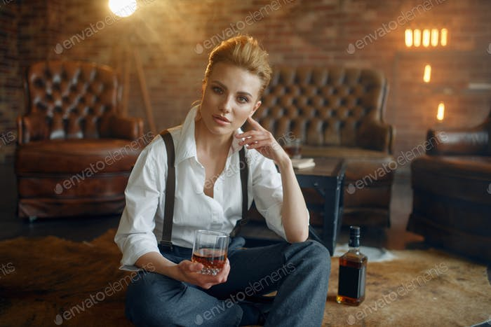 Woman sitting on the floor with whiskey and cigar