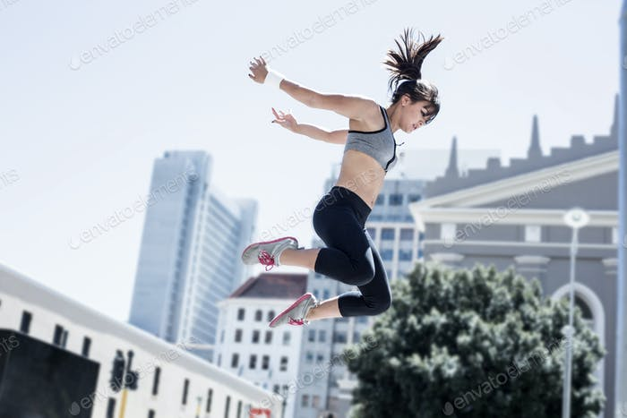 Woman doing parkour in the city on a sunny day