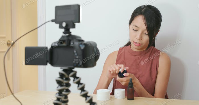 Woman taking video for beauty product at home