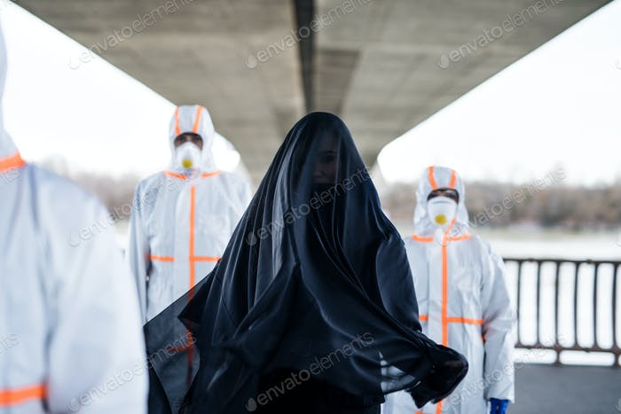People with protective suits outdoors, coronavirus and death concept.