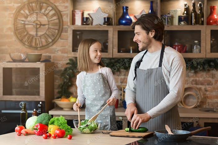 Happy father and little daughter cooking healthy salad in kitchen, cutting vegetables