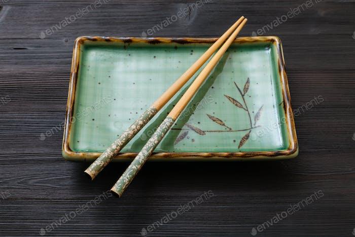 quadratischer Teller mit Stäbchen auf dunkelbraunem Brett