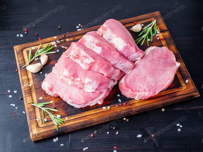 Schweinesteak, rohes Karbonatfilet auf dunklem Hintergrund, Fleisch mit Rosmarin, Gewürze, Seitenansicht