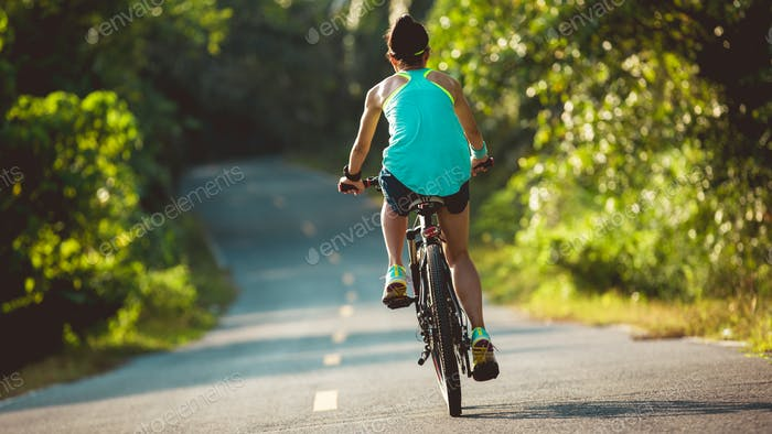 Sporty woman riding bike on tropical forest trail